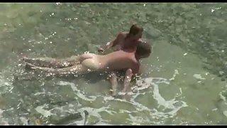 Hidden cam porno couple filmed having lovemaking in the sea on a pebble beach